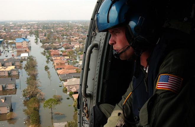 A number of survivors were shot by police and the military in the wake of Hurricane Katrina in the midst of racist media hysteria about looting. Photo of coastguard overlooking flooded New Orleans