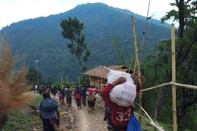People who fled fighting in northwestern Myanmar's Chin State carry supplies